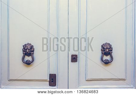 A Pair of Old Metal Lion Head Knockers on Light Blue Doors in Mdina Malta