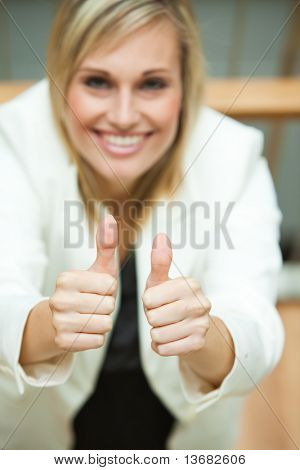 Businesswoman smiling at the camera with her thumbs up in an office