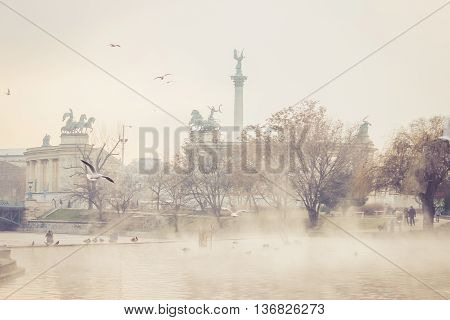 View on Heroes' Square (Hosok tere) from the City Park (Varosliget) a public park in Budapest Hungary. Thermal water in the lake is steaming in foreground. Birds are flying above the lake