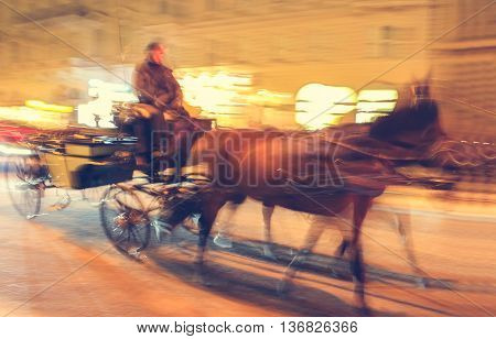 Horse carriage is running along the street of Vienna at night popular tourist attraction. Blurr in motion effect