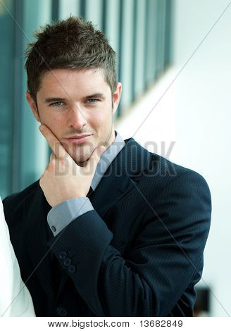 Attractive businessman smiling at the camera in workplace