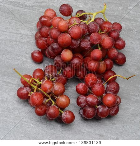 Red Seedless Grapes on a grey background.