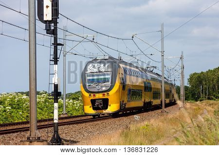 Flevoland the Netherlands - June 19 2016: Dutch intercity electric passenger train riding through the countryside