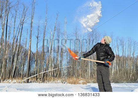teenager in clearing in winter woods vigorously tosses snow shovel