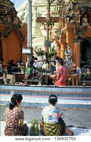 RANGOON / MYANMAR - CIRCA 1987: Buddhist worshipers pour water on the head of a sculpture of the Buddha at the Shwedagon Buddhist Pagoda in Rangoon.