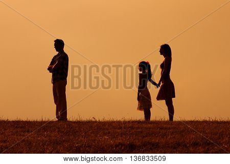Silhouette of a angry husband turning back while his wife and daughter are looking at him.