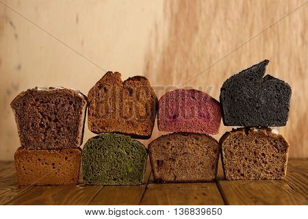 Many mixed alternative baked breads presented as samples for sale on wooden back in professional bakery: pistachio, beetroot, tomatoes, lavender, sea salt, coal, sweet potato
