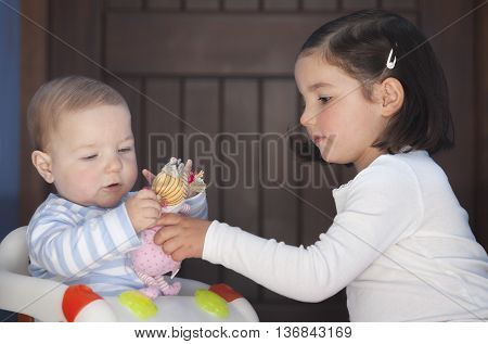 Toddler girl offering to his brother a doll. Overcoming sex stereotyping boundaries