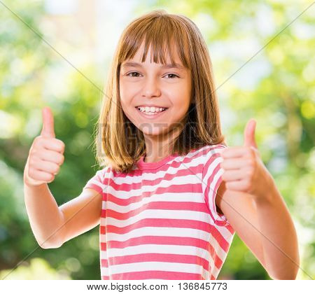 Portrait of happy girl 10-11 year old showing thumbs up gesture. Beautiful schoolgirl posing outdoors.
