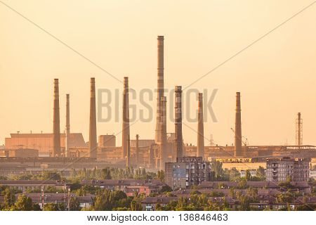 City buildings on the background of steel factory with smokestacks at colorful sunset. metallurgical plant. steelworks iron works. Heavy industry in Europe. Air pollution from smokestacks. Industrial landscape