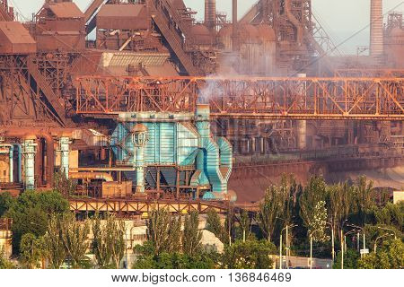 Rusty steel factory with smokestacks at sunset. metallurgical plant. steelworks iron works. Heavy industry in Europe. Air pollution from smokestacks ecology problems. Industrial landscape