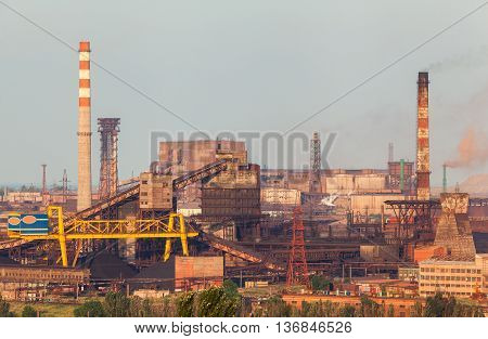 Steel factory with smokestacks at sunset. metallurgical plant. steelworks iron works. Heavy industry in Europe. Air pollution from smokestacks ecology problems. Industrial landscape