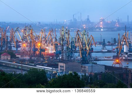 Sea commercial port at night against working steel factory in Mariupol Ukraine. Industrial view. Cargo freight ship with working cranes bridge in sea port at twilight. Cargo port logistic