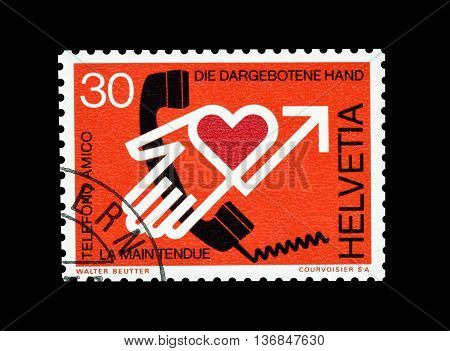 SWITZERLAND - CIRCA 1975 : Cancelled postage stamp printed by Switzerland, that shows The proffered hand.