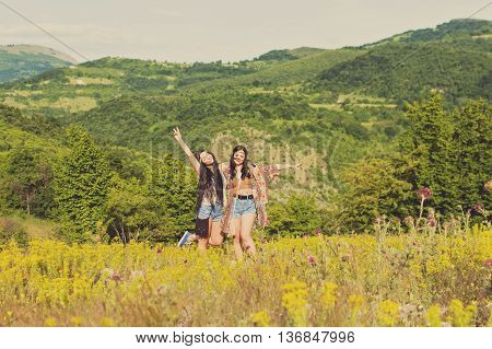 Two cheerful boho hippie style sisters in nature on sunny summer day. Two young female friends having fun outdoors. Mild retouch, mild filter, natural light.