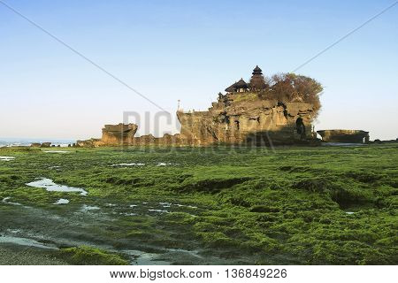 A shot of mossy at Tanah Lot Bali Indonesia during low tide and with sunsrise scenery.