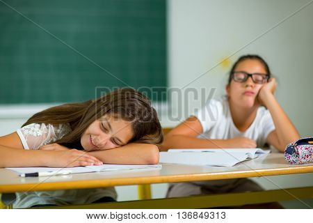 Two girls are bored in class at school