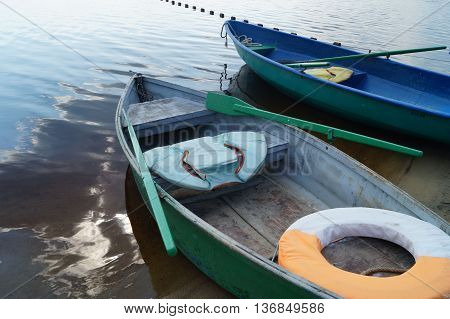 green and blue boats on the river with oars and a lifeline