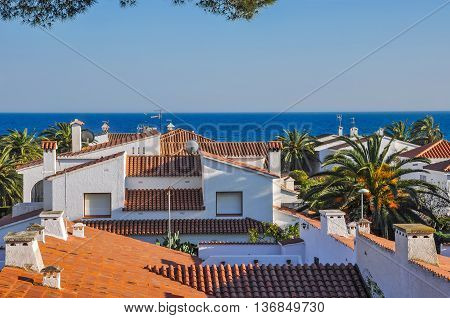 Sea view atop of terracotta tiles roofs. Travel destination. Summer vacations concept. Costa Dorada Spain. Horizontal.