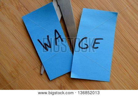 employee wage cuts illustrated with scissors and a note