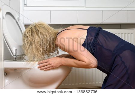 Blond Woman Vomiting Into A Toilet