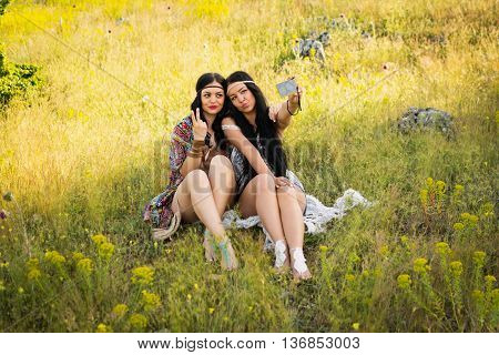 Two hippie sisters taking a selfie on smartphone outdoors on sunny summer day. Two beautiful young women taking a photo using cellphone. Natural light, no retouch, no filter.