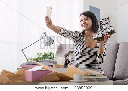 Smiling woman unboxing a postal parcel and taking a selfie with her new purchases using a smartphone poster