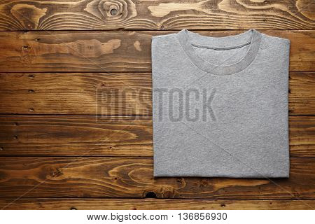 Blank grey t-shirt accurately folded on rustic wooden table top view mockup