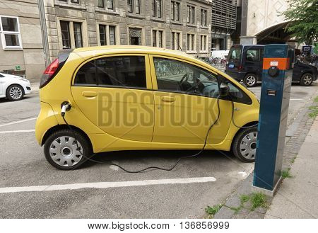 COPENHAGEN DENMARK - CIRCA JUNE 2016: yellow Mitsubishi electric car recharging on the street