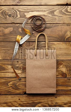 Brown takeaway bag from thic recycled craft paper on rustic wooden table near unrolled vintage tailoring meter mockup