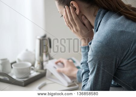 Sad depressed woman at home sitting on the sofa she is calling an help line with her phone