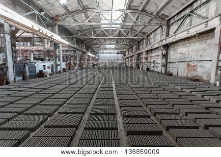 Stack of bricks. Manufacturing of aerated concrete blocks. Manufacturing of cinder block. The plant manufactures building material. The plant produces a cinder block. Cinder block-building material.