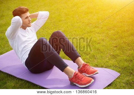Fit young man doing sit-ups with efforts. He is sitting on mat on grass