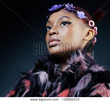 young pretty african american woman in spotted fur coat and flowers jewelry on head smiling sweet etnic make up bright closeup fashion
