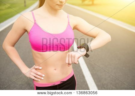 Skillful female runner using smart watch while training. She is standing with arm akimbo on road
