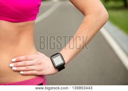 Close up of female hand with tracker. Young sporty woman is standing with arms akimbo