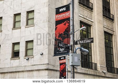 New York, USA - June 18, 2016: Wall street and Nassau street sign post crossing with NYC banner sponsored by BGC partners