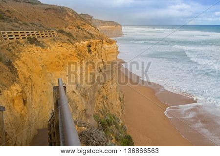 Partial view of 86 step wooden staircase beach access at Gibson Steps down the cliff to the seashore in Port Campbell National Park on the Great Ocean Road in Victoria, Australia