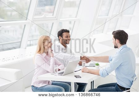 Welcome to team. Two men shaking hands and looking at each other with smile while their coworker sitting near them