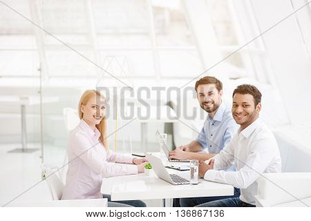 Working diligently to meet the deadline. Young business team in modern office during meeting, looking at camera and smiling