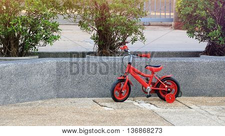 red bicycle for children leaning against the wall