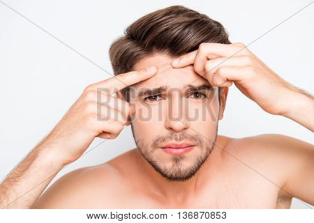 Close up photo of young man looking for acnes on his face poster