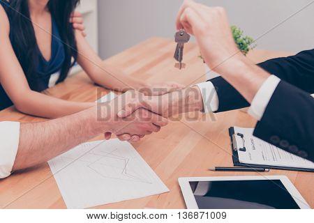 Close Up Photo Of Handshake. Broker Giving Keys Of New  House