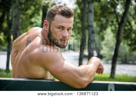 Handsome Muscular Shirtless Hunk Man Outdoor in City Park. Showing Healthy Muscle Body While Looking at Camera, Sitting on Bench