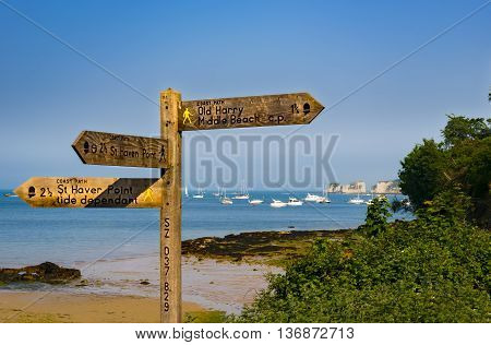 Wooden signpost and blue seas in Dorset