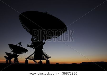Huge Antenna Dish at Very Large Array Radio Observatory Silhouetted at Sunset