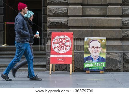 Melbourne, Australia - Jul 2, 2016: People walking pass polling place in Melbourne during Australian federal election 2016, with billboards promoting candidates from Labor and Greens parties.