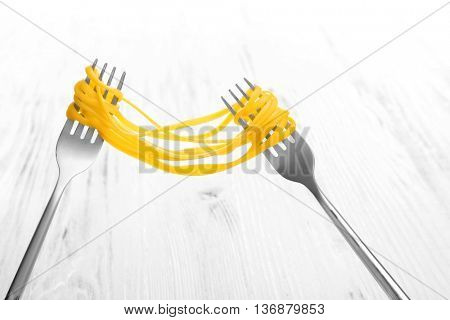 Forks with cooked pasta on white wooden background