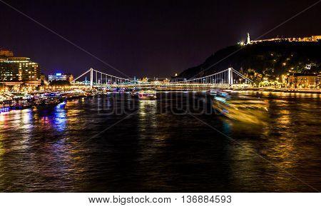 Cruise Boats Danube River Passing Under Chain Bridge Night Budapest Hungary. Elizabeth Bridge in the distance