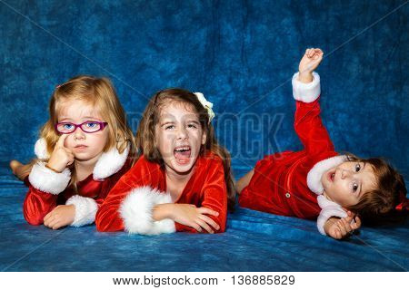 Three sisters lay on a portrait studio floor. One cooperates with the photographer and smiles one scratches at her eye and one makes silly faces as she rolls around the floor.